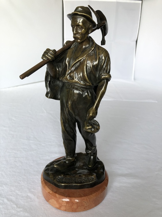 bronze figurine of a farmer with a brown marble base against a white backgound