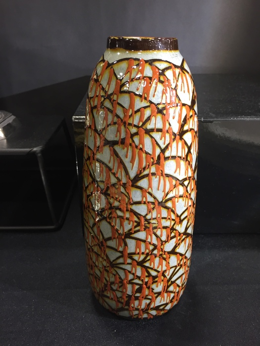 orange grey and brown pottery vase with abstract design against black fore and backgound