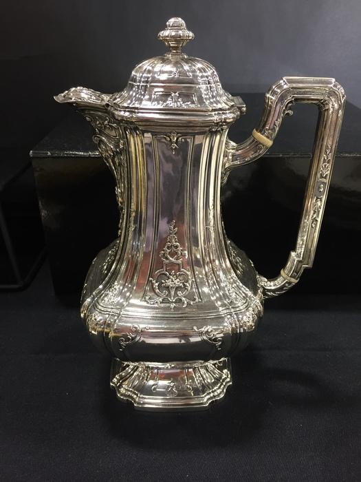 sterling antique coffee pot against black fore and background