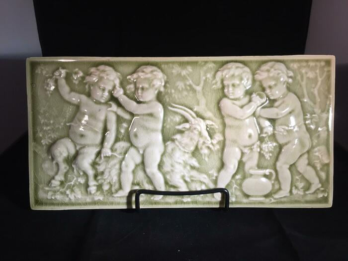 green ceramic tile with putti